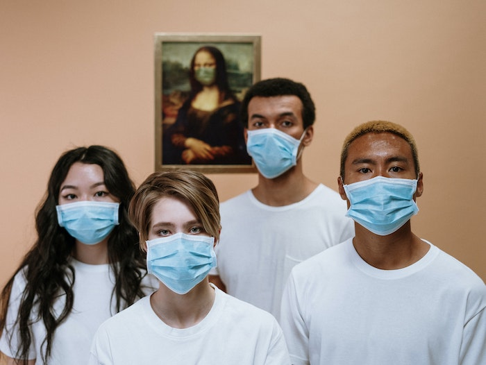 Four young people in white T-shirts and blue surgical masks stand in front of The Mona Lisa, and she also appears to wear a mask.