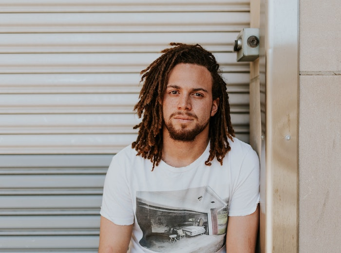 A young light-skinned Black man with neat dreadlocks wearing a vintage T-shirt looks at the camera.