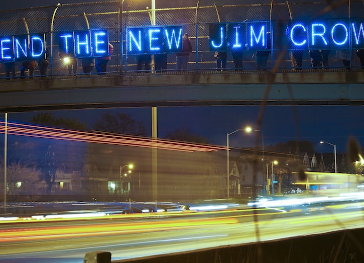 "Neon blue letters hang on an over pass and read ""End the New Jim Crow."""