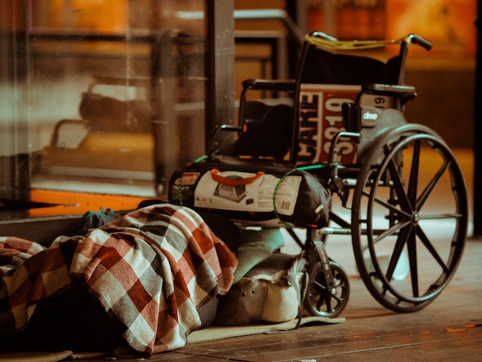 An empty wheelchair beside a plaid blanket suggest a homeless person sleeps beneath it.